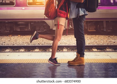 Legs Loving Couple happy hugging in the train station of a country after arrival in summer with a warm sunlight background.