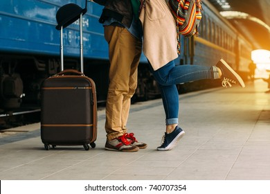 Legs Loving Couple happy hugging in the train station of a country after arrival in autumn with a warm sunlight background. Trolley broun bag. Travel concept