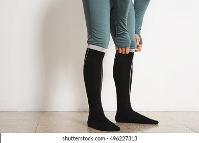 Legs of male athlete in winter baselayer and black long thermal socks