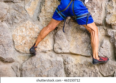 Legs of male rock climber clings to a cliff