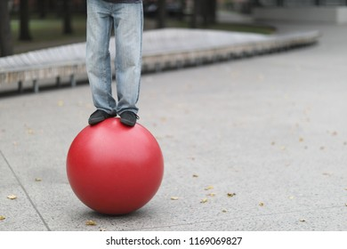Legs of a man of a balancing actor standing on a big red ball