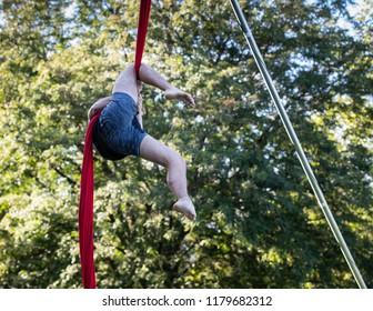 Legs of man hanging on red ribbon