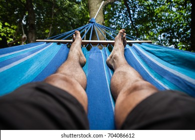 Legs of a man lying on a hammock in the woods. Illuminated from above.