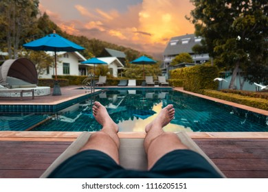 legs of man - male tourist lies on a beach chair during sunset in the swimming pool area of the hotel facility