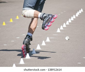 Legs of a man performs the trick on  roller skates
