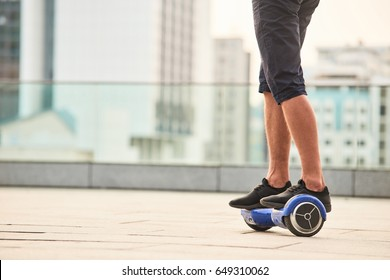 Legs of man riding gyroboard. Person on blue hoverboard. Facts about hoverboards.
