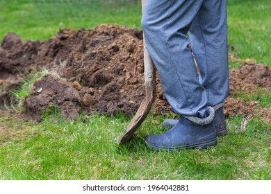 Legs of a man in rubber boots with a shovel near the excavated ground close-up. Hard work, farming, gardening, reforestation. Landscaping. Digging a grave, burial. Copy space.