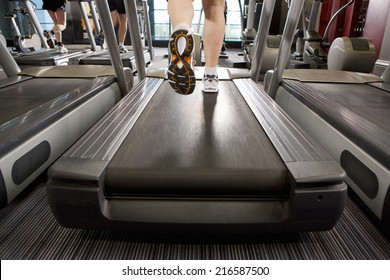 Legs of man running on treadmill in health club