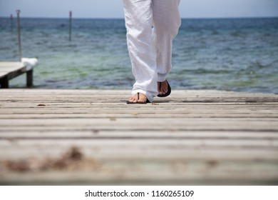 The legs of a man in sandals and white trousers walk on a wooden pier on the Mediterranean coast