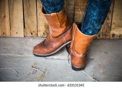 Legs of man wearing boots standing in barn