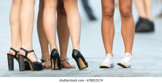 Legs of meeting women on the street. Intentional focus on central leg