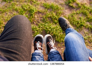The legs of mom, dad and child on the background of green grass. The family spends time together. Spring Time