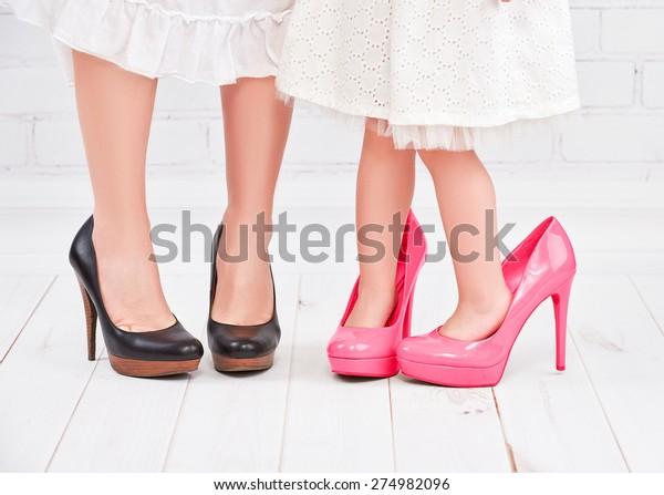 benen moeder en dochter meisje fashionista in roze schoenen op hoge hakken