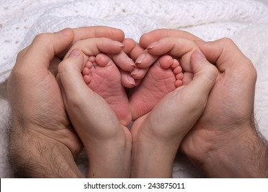 Legs newborn baby hands hug mom and dad, forming a heart. Symbolizes love, unity, caring, tender to the baby