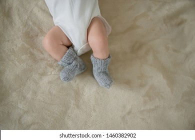 Legs of a newborn in a white body and gray socks, on a beige background.