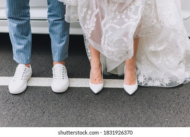 Legs of newlyweds close-up in fashionable white leather shoes on an asphalt road against the background of a car. Photography, concept, copy space.
