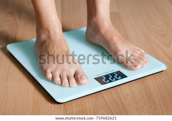 Legs on the scales. Checking the weight. Losing weight.