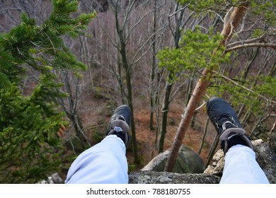 Legs on the top of the rocky hill, high mountain and person sitting on the top of it with abyss below legs. Human legs hanging above the abyss, as seen from above. Hiking in the mountains sport boots.