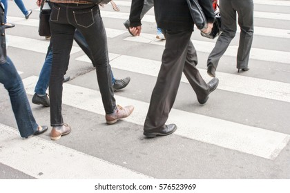 legs of pedestrians in a crosswalk on summer day