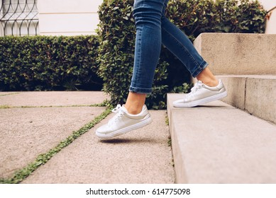 Legs of pretty woman in the sneakers walking downstairs. Horizontal outdoors shot.