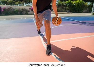 Legs of a professional basketball player dribbling the ball on the basketball field. Summertime during hot day