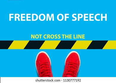 Legs in red sneakers on a blue background a restrictive yellow and blak stripe with text not cross the line and text Freedom of speech. Concept of restricting freedom of speech. Flat lay, top view.