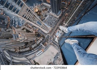 Legs of roofer on skyscraper near Dubai Marina Canal at sunny day in Dubai, UAE
