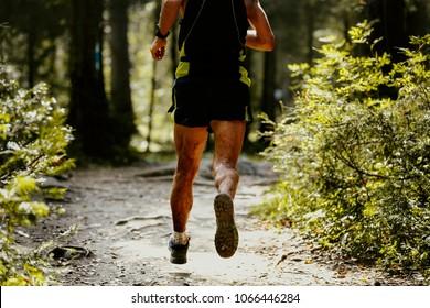 legs runner athlete in spray dirt forest trail run