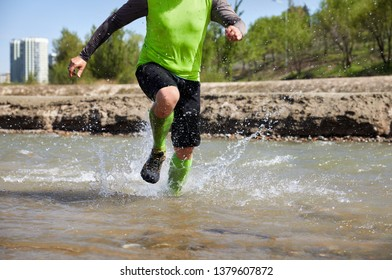 Legs of runner close up the river with splashes