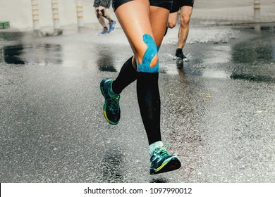 legs runner woman with kinesio tape and compression socks
