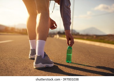 Legs and running shoe closeup of man jogging outdoors on road.Selective focus
