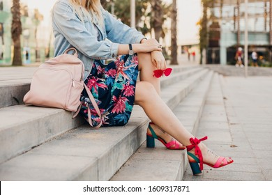 legs in sandal shoes of stylish woman sitting on stairs in city street in printed skirt with leather backpack holding sunglasses, summer style trend
