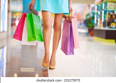 Legs of shopaholic wearing blue dress while carrying several paperbags