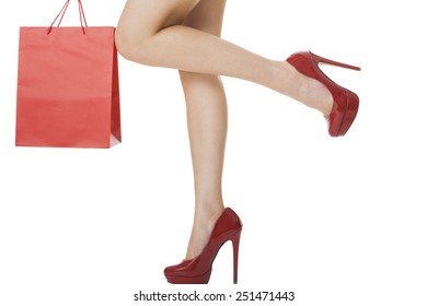 Legs Shot - Woman Legs with Flawless Skin in Red High Heels Shoes Lifting One Leg While Carrying Red Paper Bag. Isolated on White Background.