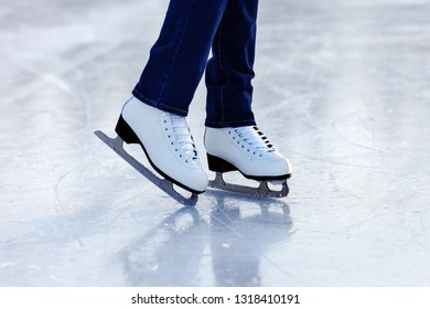 Legs of skater girl in skates on the rink in winter