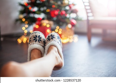Legs in slippers on Christmas tree background