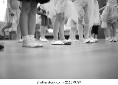 Legs of small girls in gymnastic slippers and fluffy skirts; monochrome