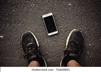 Legs and a smartphone with a broken screen on a dark background. The view from the top.