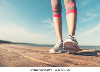 Legs in sneakers close-up. Health and Yoga Concept. Rear view close up strong athletic female legs and running shoes of sport. Sporty young girl practicing yoga. Woman do gymnastics outdoors