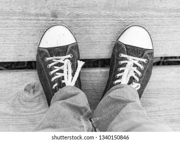legs in sneakers on a wooden floor