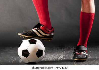 legs of soccer player with ball on dark background