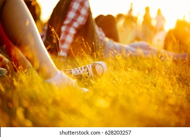 legs in sport shoes or sneakers in grass. summer lifestyle. Colorful warm yellow toning. People on holiday laying on ground. recreation in park nature. Music Festival on outdoor. Object photo.