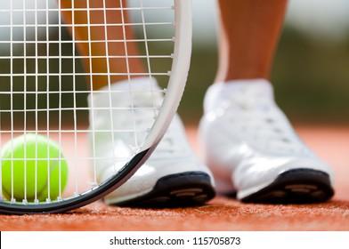 Legs of sportive girl near the tennis racquet and balls