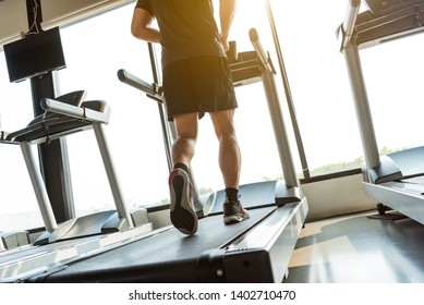 Legs of sportsman running on treadmill in fitness gym center. Sport and Healthy lifestyle concept. People workout and exercise activity. Back view or rear view
