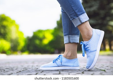 legs step of a girl in jeans and blue sneakers on a sidewalk tile, a young woman strolling in a summer park, a concept rest and everyday style