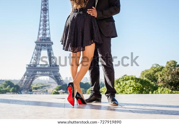 Beine des stylischen Ehepaares, das einander umarmt, und der Eiffelturm im Hintergrund