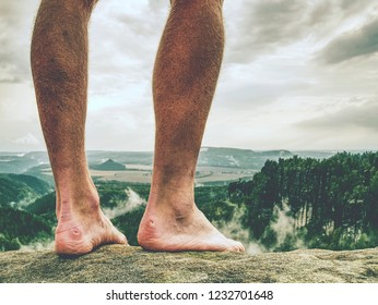 The legs take a rest on tiring mountain trail. Sweaty male legs without trousers relaxing on peak of mountain above valley.