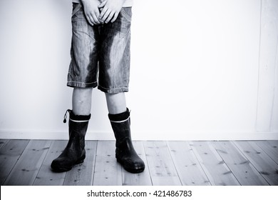Legs of teenager in short jeans pants wet with water or urine standing on hardwood floor with copy space on wall