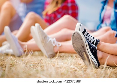 Legs of teenagers, canvas shoes, summer music festival. Young teens at summer music festival. Funny group of young girls and boys at music festival. Happy teen at summer festival.