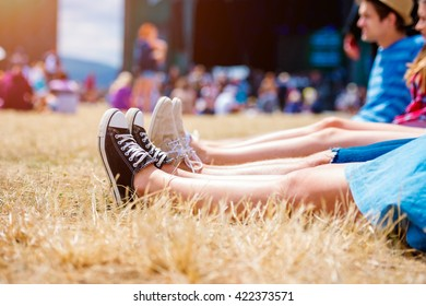 Legs of teenagers, music festival, in front of stage. Young teens at summer music festival. Funny group of young girls and boys at music festival. Happy teen at summer festival.